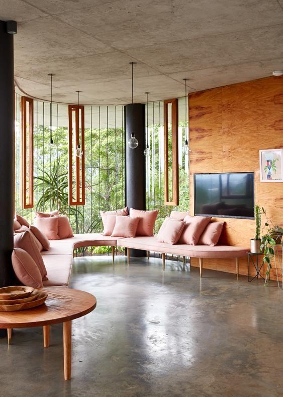 Jungle Fever. Sembra quasi un bovindo la zona lounge che segue il profilo curvo della vetrata. Un po' designer, un po' architetto, Jesse Bennett si è divertito a disegnare e realizzare i mobili su misura che arredano Planchonella House, come questo divanetto nei toni cipria.