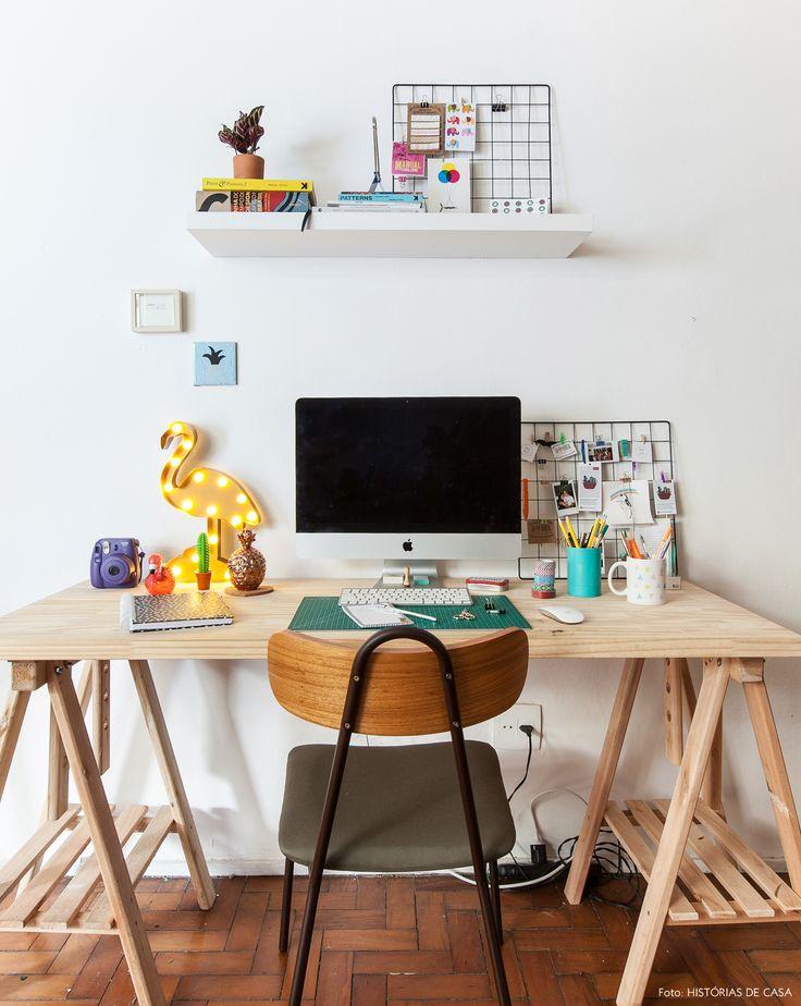 Espaço de trabalho tem placa de madeira pinus sustentada por cavalete.