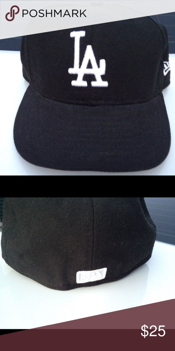 """(Slightly Used) Men's LA Dodger Black Baseball Hat (Used). Like new. Men's LA Dodger Baseball Hat. Color: Black with White """"LA"""" Logo. Size: 7 1/8"""". Item has been in storage. Not stored properly - just a little misshapen but not ruined. Once on a head it looks fine. Brand: New Era 59Fifty. Smoke and pet free home. ***PLEASE NOTE ALL CLOSET ITEMS INCLUDING THIS PIECE WILL ONLY BE AVAILABLE FOR SALE UNTIL THE END OF NOVEMBER. I WILL REMOVE AD AFTER THAT TIME.*** New Era 59Fifty Accessories Hats"""
