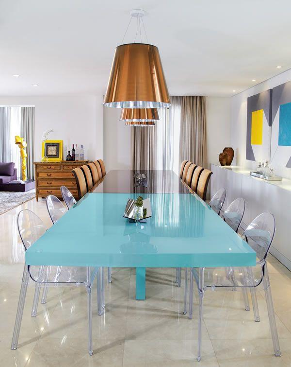 Clássico com Moderno... Um charme...A sala de jantar e a copa são integradas e o que diferencia os dois ambientes é a cor da mesa e o estilo das cadeiras. Na copa, a mesa é em laca azul-turquesa e as cadeiras são de acrílico transparente. Na sala de jantar, a mesa tem tampo em vidro espelhado bronze e cadeiras de madeira com estofado em tecido nude. Gosto da proposta de integrar os ambientes e diferenciar pelos acabamentos.