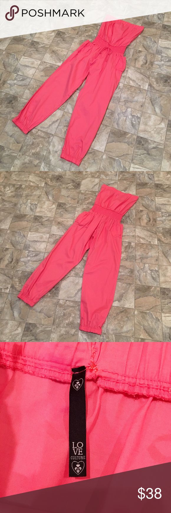 """LOVE CULTURE coral jumpsuit LOVE CULTURE coral strapless pant jumpsuit   stretchy waist   stretchy tapered bottoms   pockets on the sides   size S   inseam is 27""""   waist measures 10.75"""" across, is stretchy and stretches a few more inches   top measures 13.5"""" across, also stretchy and stretches a few more inches   had a tiny hole at the top in the back that was sewn up - not noticeable when worn! Love Culture Pants Jumpsuits & Rompers"""