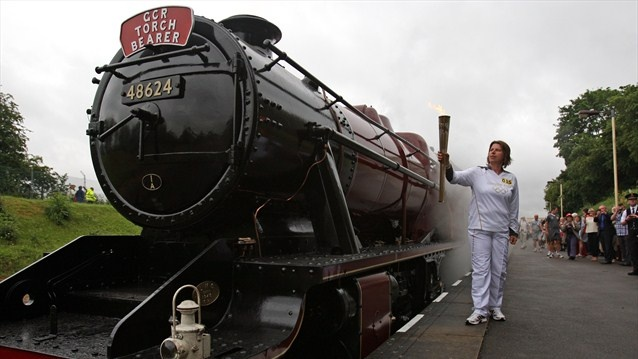 Torchbearer Angela Conibear holds the Olympic Flame next to a steam train before the Flame takes a journey on the Great Central Railway during Day 46 of the London 2012 Olympic Torch Relay.