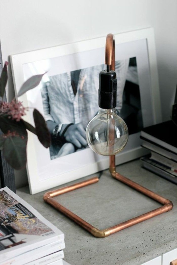 une lampe au chevet au design épuré, fite de tuyau cuivre et ampoule