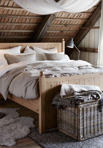 Camera da letto con struttura letto in legno, biancheria da letto e cuscini nei toni naturali e in bianco.