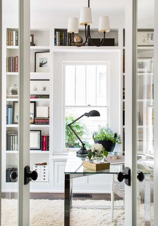 This home office with clean white bookcases, a sheepskin rug, and a glass desk is stylish, contemporary, and beautiful.