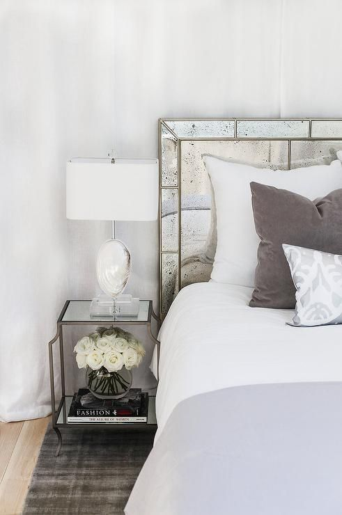 Alyssa Rosenheck - Ashleigh Meier Design - Restful bedroom boasts a mirror top metal nightstand placed on a gray velvet rug and lit by a white agate lamp positioned beside a bed dressed in white bedding draped in a gray pillow and topped with a gray velvet pillow and a silver damask pillow placed in front of an antiqued mirrored headboard.