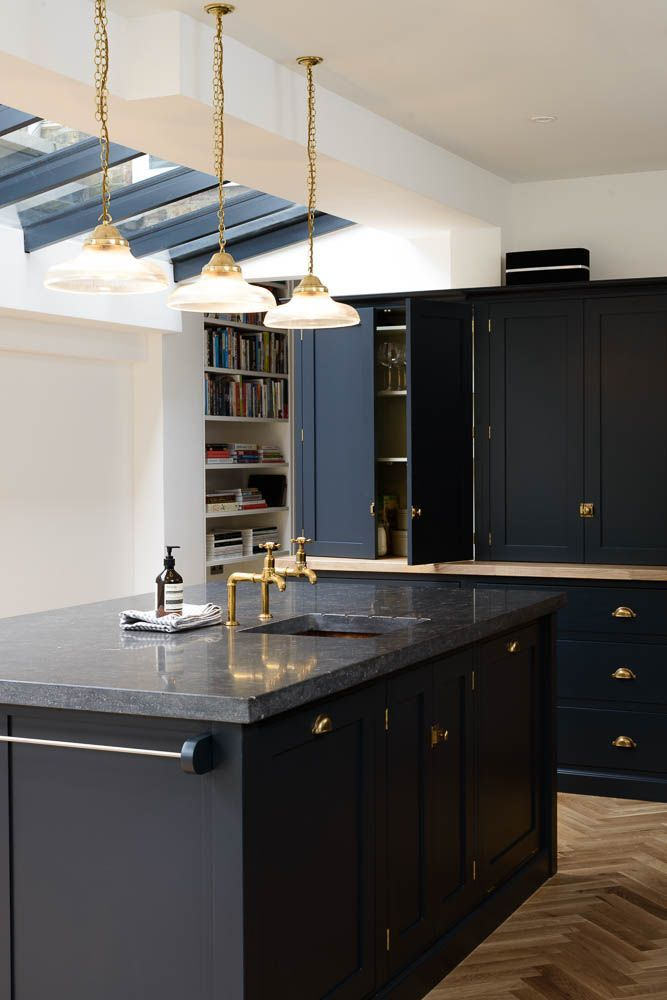 This beautiful big island makes the perfect centerpiece to this stunning brass and navy blue Shaker kitchen with parquet flooring, granite countertops and sneaky storage solutions.