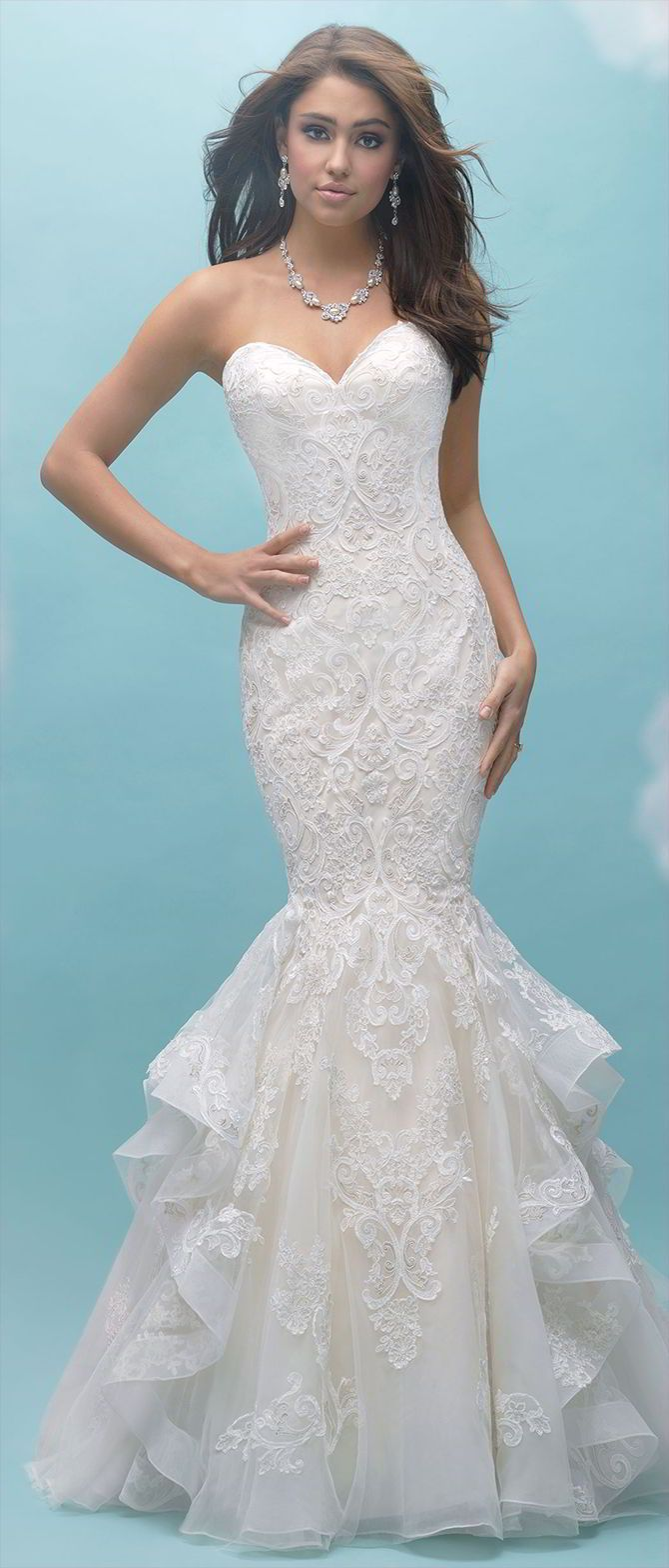 This strapless, ruffled mermaid gown features symmetrical patterned lace across the bodice and train.