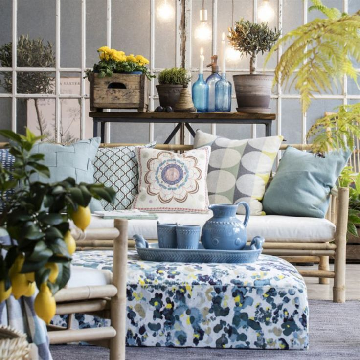 Mixed patterns and tones of yellow and blue.  This living room is decorated with furniture that fits both inside and in the conservatory.  Pillows from Afroart.