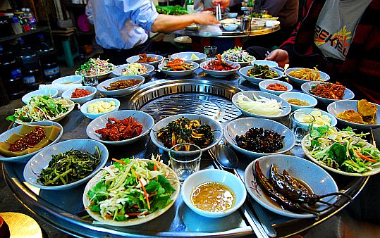 southkoreanfood:Table setting around a Korean BBQ grill. To meet standards, the many complimentary side dishes (Banchan 반찬, varies by location & restaurant) arrives before the main food!