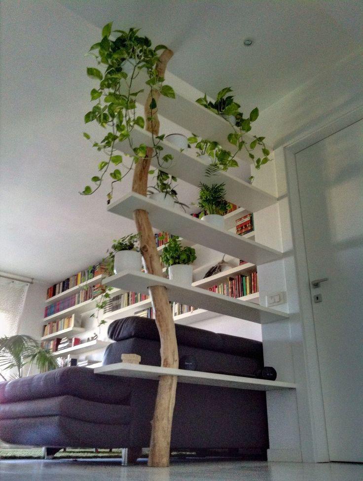 Tronc d'arbre qui traverse les étagère + dessence de fausses plantes = belle séparation végétal moderne