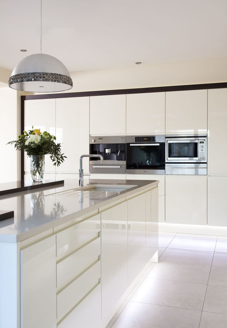 Sleek lines with this white gloss handleless kitchen and Silestone worktops.