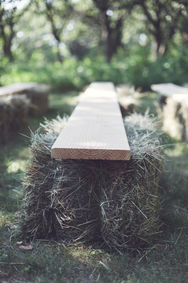 rustic ceremony seating. hay bales and wood planks