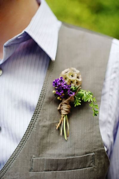 The groom's boutonniere will be a scabiosa pod with purple waxflowers and hints of greenery wrapped in twine with the stems showing