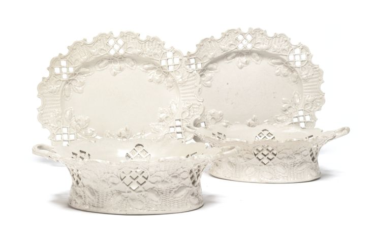 A PAIR OF STAFFORDSHIRE WHITE SALT-GLAZED STONEWARE RETICULATED OVAL BASKETS AND STANDS, CIRCA 1765 the exterior of the baskets and the rim of the stands molded with basketwork, the pierced cartouches issuing branches of leafy grapes and pears beneath the valanced edge. length of stand 10 1/8 in