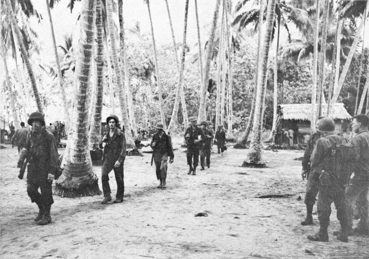 U.S. Soldiers march through Hariko on their way to the attack at Cape Endaiadere on 21 Nov. '42. It is very likely that these are from 1ST Bn., 128TH Inf.; they were to attack Cape Endaiadere from along the coast. The 3D Bn. was to advance along an inland trail. The 2D Bn. was the reserve and was supposed to follow 3D Bn.