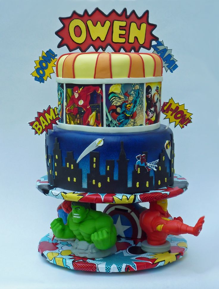 "Superheroes Unite! - MMF covered with fondant details and edible images. Small BAMS are gumpaste placards, top is fondant with a candy melt backing attached to lollipop sticks. Base was preconstructed using 4 PVC ""money banks"" hiding threaded rods supporting the upper cake load."