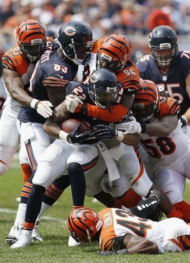 Chicago Bears running back Matt Forte (22) is tackled by Cincinnati Bengals defensive end Carlos Dunlap (96), linebacker Rey Maualuga (58) and safety George Iloka (43) during the first half of an NFL football game, Sunday, Sept. 8, 2013, in Chicago. (AP Photo/Charles Rex Arbogast)