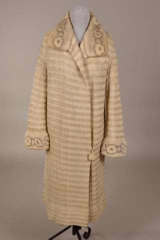 "White wool coat, American, 1925-1927. This woman's coat has knit strips of white wool yarn and white silk floss. The collar and cuffs are of white chenille with flowers of white chenille edged with grey chenille. There is one button at the lower left front. Label: ""Pack-Wolin, Detroit."""