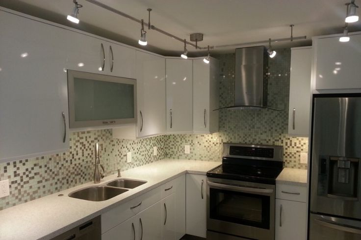 mosaic tiled backsplash flat panel cabinet white cabinet undermount sink stainless steel aplliances bar lights metal hood of Renovating Your Condo Kitchen with These Stunning Designs