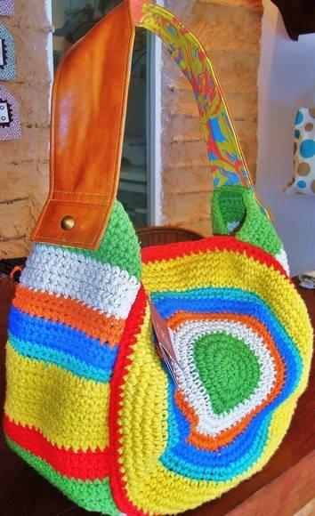 Uma bolsa em crochet, feita à mão, com alça em couro dourado, toda forrada em tecido de algodão estampado. R$ 189,00