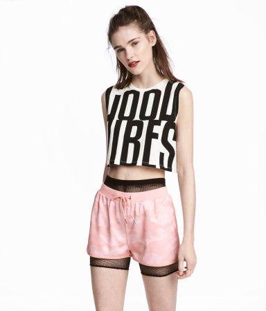 Hellrosa. Kurze Shorts aus Retromaterial mit Musterdruck. Die Shorts hat einen elastischen Rippenbund mit Kordelzug und seitliche Taschen. Einfassungen und