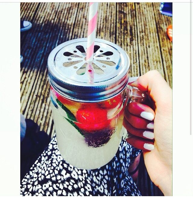 Drink jars with lemonade and fruits, flower lids and stripey straws