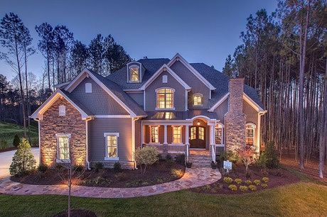 Stone accents and a stone chimney and walk lead to this home sheltered by tall pines. The Wrenhurst community. New homes from Baker Residential in Cary, NC.