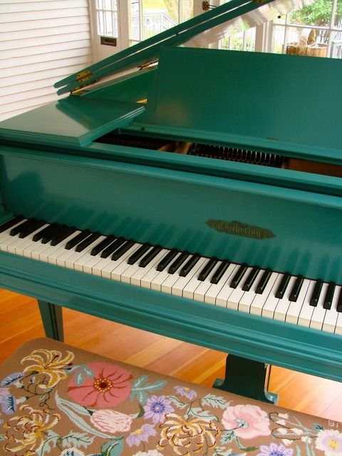 It's a teal piano. With an embroidered bench. On a sun porch <3