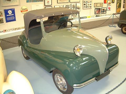 "1951 Kover. The Societe Industrielle de Livry, having introduced the Atlas in 1949, brought out a 2nd vehicle at the Paris Salon of 1951.  It too adopted the two-seat roadster ""pedal car"" style of the Atlas, Rolux and Rovin D-2. It utilized the same ""house"" chassis & AMC motor as the Atlas, incorporating a separate gearbox and incorporated a reverse. The body was a little more ""downscale"" than the Atlas, with no doors and lights perched on top of the fenders rather than built-in."