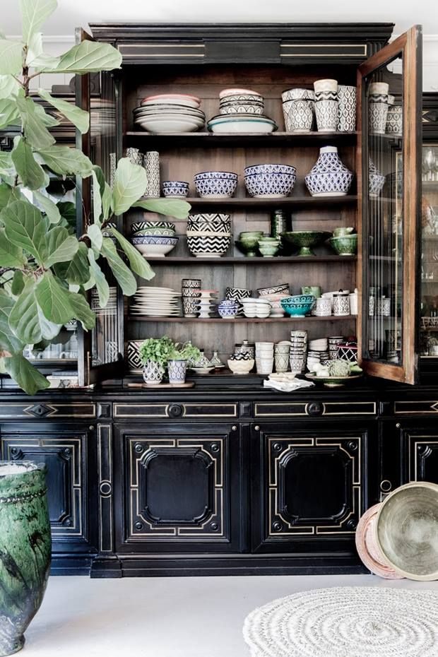 """Black cabinet makes an appealing """"frame"""" for a motley of patterned dishes"""