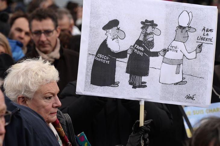 Une femme à Strasbourg brandit un dessin de Siné figurant des représentants de l'islam, du judaïsme et du catholicisme avec les mots « obscurantiste », « fanatique », « intégriste ». Crédits : AFP/PATRICK HERTZOG En savoir plus sur http://www.lemonde.fr/societe/portfolio/2015/01/11/les-meilleurs-slogans-des-manifestations-en-hommage-a-charlie-hebdo_4553824_3224.html#XS4Ao6dt3s3yHwzd.99