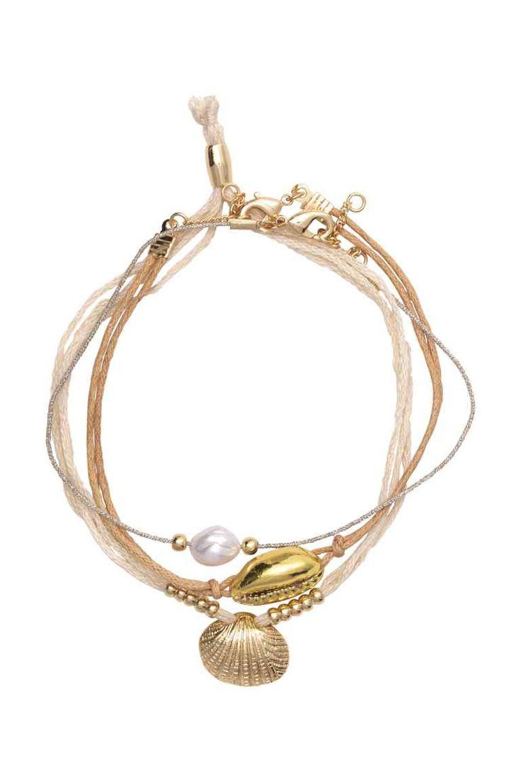 Lot de 3 bracelets: Bracelets en textile. Modèle orné de perles fantaisie et de pendentifs en coquillage, métal et plastique.