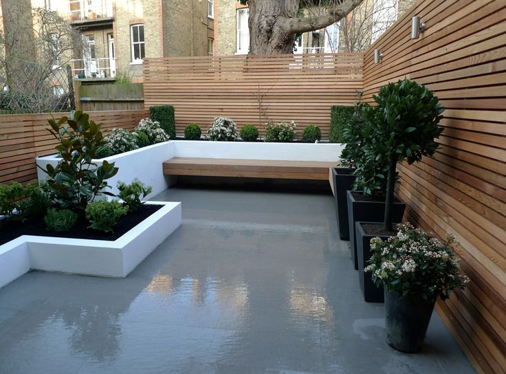 Smooth grey paving tiles, cedar hardwood privacy screens, balau hardwood floating corner bench, raised rendered and white washed walls combine to create a fresh and exciting small London garden.