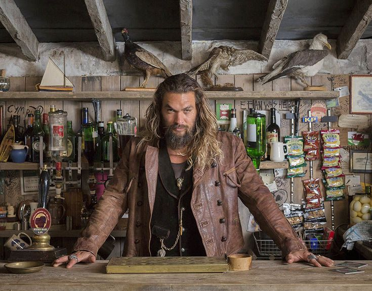 Jason Momoa who plays Aquaman stands at a bar at The Justice League Experience