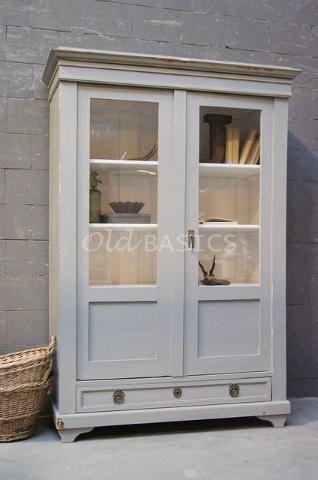 Vitrinekast 10125 - Landelijk vormgegeven vitrinekast in een lichtgrijze kleur. Achter de deuren is de kast wit en er zitten drie vaste legplanken. Onderin een lade met prachtige slot plaatjes!