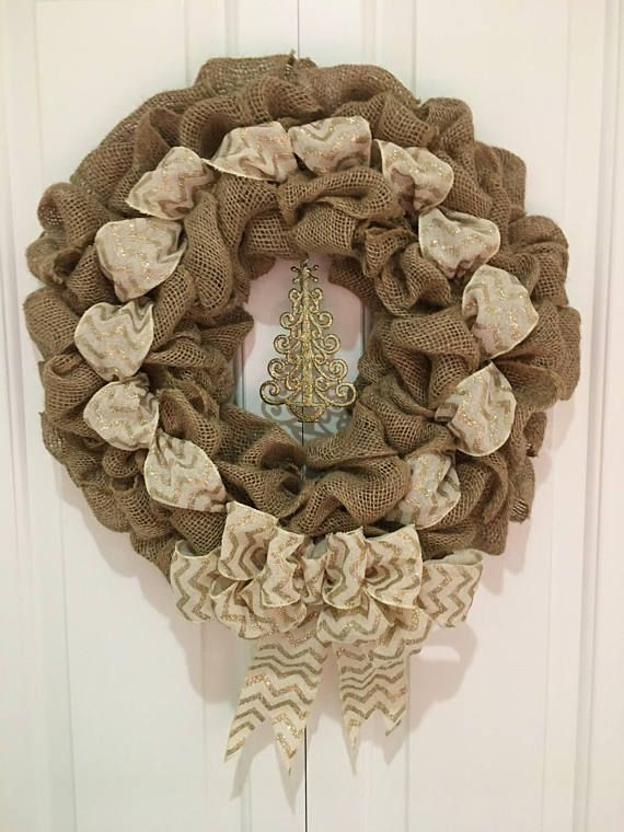 "This beautiful hand made burlap wreath is accented by an ivory and glittery gold chevron ribbon and large bow. Hanging in the center is a glittering gold Christmas tree. The perfect wreath for any holiday party. This wreath measures approximately 22""in diameter. Customize your"
