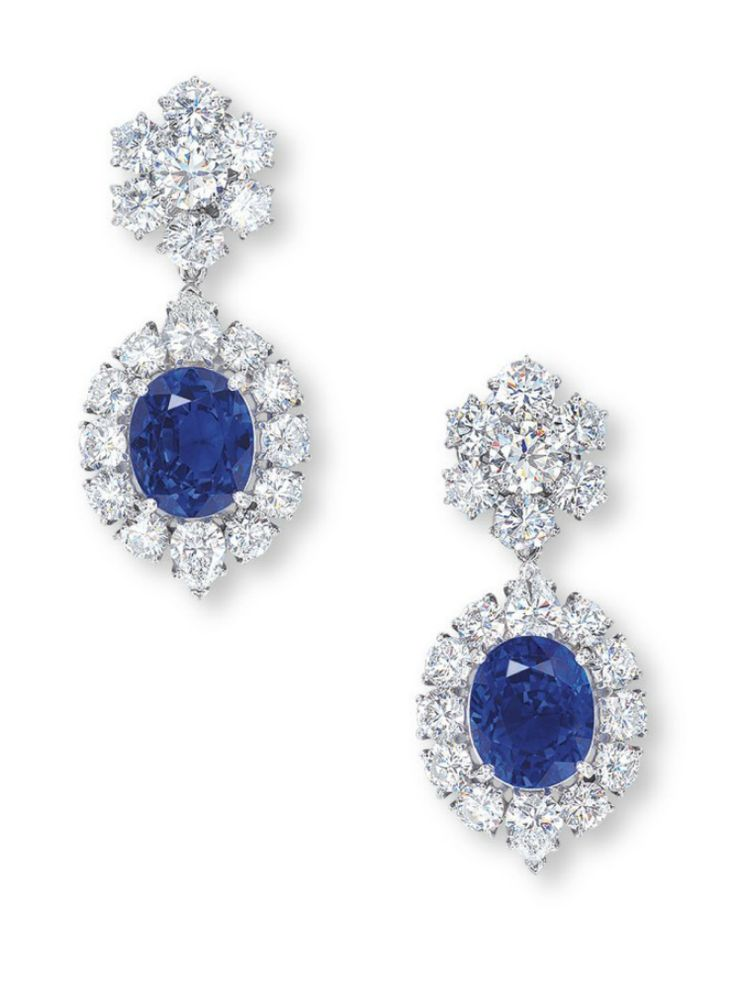A PAIR OF SAPPHIRE AND DIAMOND EAR PENDANTS, BY VAN CLEEF & ARPELS Each set with an oval-shaped sapphire weighing approximately 9.45 and 8.09 carats, within a brilliant and pear-shaped diamond surround, joined to the brilliant-cut diamond floral surmount, mounted in platinum, 4.0 cm long