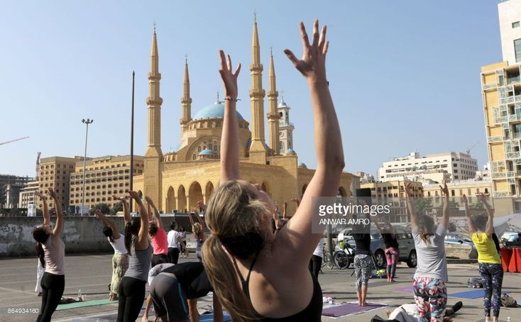 Lebanese men and women practice yoga during the special '108 Sun Salutations' event in the capital Beirut's Martyrs Square on October 22, 2017. /