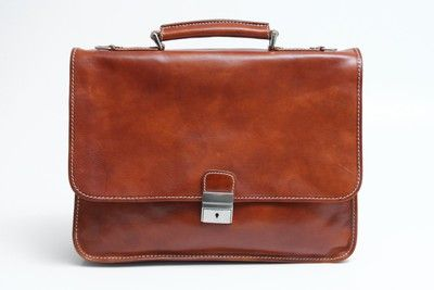 Padova Leather briefcase is big enough to hold a laptop, files, a newspaper, and notebooks. It is divided into two compartments for easy organization and has an additional outside pocket. The top swings open for easy access to all of your files and has a locking buckle strap to secure it. Handmade in Tuscany using Italian polished calf-skin leather and old world craft methods, the result is a timeless and simple briefcase with unquestionable quality and durability.