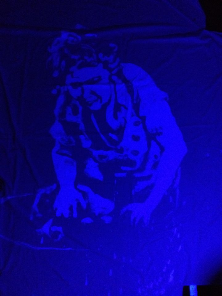 Washerwoman painted on a bed sheet in washing detergent. Image visible only under ultraviolet light as the optical brighteners fluoresce.