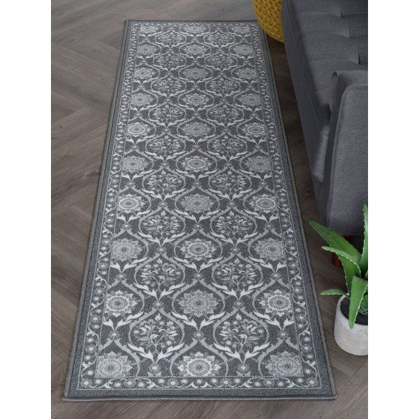Sweeten traditional or transitional décor with this versatile floral area rug. Ribbons and blossoms form a printed brocade pattern. Power loom, machine made of looped nylon yarn to be durable and affordable. Non-skid backing keeps it from sliding on wood, laminate, polished concrete and tile floors, making this ideal for the kitchen, entryway, bathroom or family room.