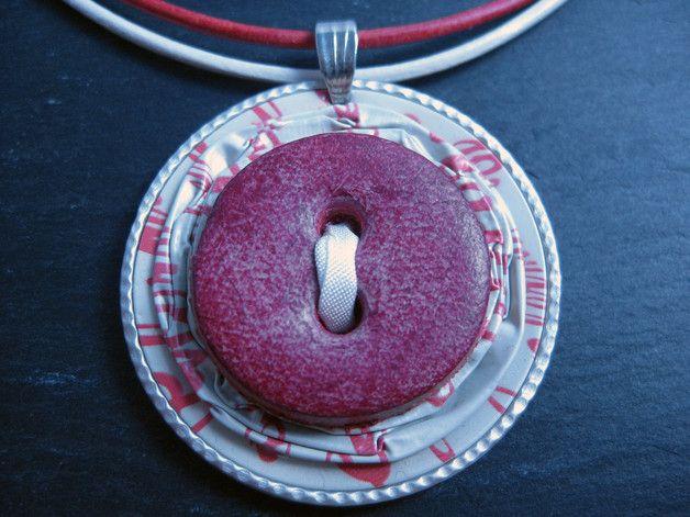 Die Kette besteht aus einem weißen und einem roten Lederband mit Karabiner-Verschluss und Verlängerungskettchen sowie einem Anhänger aus Nespresso-Kapseln, auf dem ein roter Lederknopf mit einem...