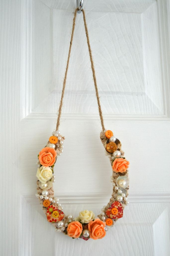 pretty horseshoe , wedding gift, hessian ribbon binding, apricot/coral and ivory shades . decorated with wooden heart buttons, pearl buttons in classic pearls and apricot/coral pearls in two sizes. twist of pearls around the whole horseshoe. ivory foam soft touch roses, and pearlised buttons . these are made on a genuine metal horseshoe, so the …