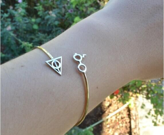 This elegant bangle is made from beautiful bent metal that has been molded into a wrap-around shape. The bangle is designed to look like Harry Potter's infamous round glasses complete with Potter's li