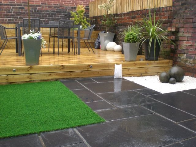 Garden makeover in Sheffield including black limestone patio, artificial lawn, decking and raised sleeper planters