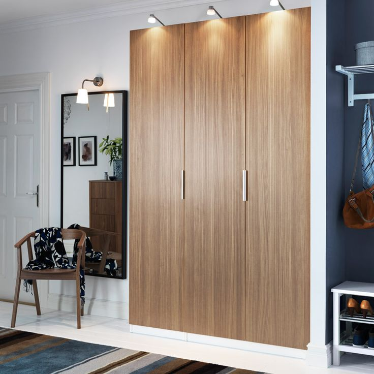 PAX white wardrobe with STOCKHOLM walnut veneer doors and IKEA STOCKHOLM nickel-plated cabinet lighting