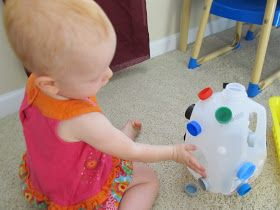 put velcro circles on the outside of a clean, empty milkjug and used lids from milk, soda bottles, etc. to stick all over it, cut a circle in the side of the jug to put lids in and the child can tip the caps out too - Containment and positioning schemas