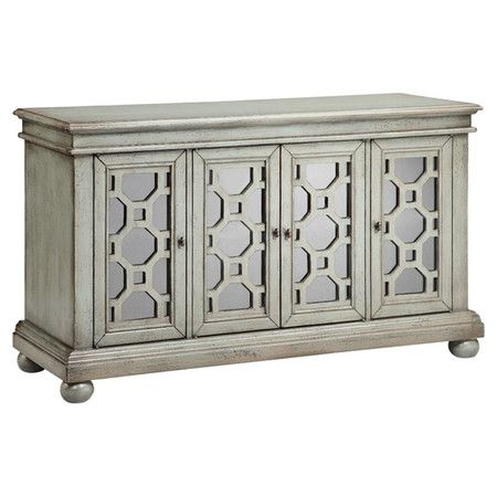 Stow extra table linens and place setting in eye-catching style with this weathered sideboard, featuring mirrored doors with geometric overlay.