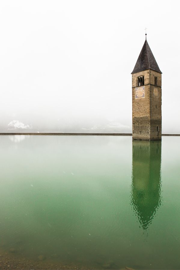 steeple of submerged 14th century church in Lago di Resia / Lake Reschen, South Tyrol, Italy